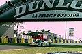 Dauer 962 LM - Hans-Joachim Stuck, Thierry Boutsen & Danny Sullivan under the Dunlop Bridge at the 1994 Le Mans (31970255555).jpg
