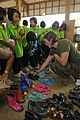 Defense.gov News Photo 110207-M-9683P-237 - U.S. Marine Corps 1st Lt. Johanna Ciezczak with 3rd Marine Logistics Group fits a student with donated shoes during exercise Cobra Gold 2011 at.jpg
