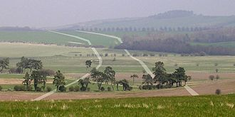 Dorset Cursus - A view northeast from Gussage Down towards Bottlebush Down - the approximate course of the Cursus banks are superimposed in white. The round barrows on Wyke Down can be seen in the centre of the photo. The cursus has a slight change of direction as it climbs Bottlebush Down and it is thought that the original terminal of the cursus was at this point (and was later extended another 4.5 km north-east to Martin Down).