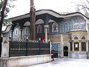 Photo of old two-storey building covered in blue Iznik tiles, with a prostyle portico and windows on the upper storey