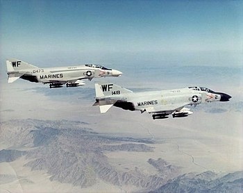 A pair of armed Phantom jet fighters in flight at high altitude
