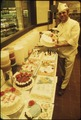 GERMAN IMMIGRANT HANS STRZYSO IS THE CHIEF BAKER AT MADSENS SUPERMARKET. HE SPECIALIZES IN ALL TYPES OF DECORATED... - NARA - 558347.tif