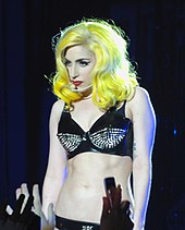 A young woman on stage. She wears a bright yellow wig and a black bra with embroidery.