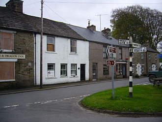 Garrigill - View of row of houses including the Post Office. The boarded-up pub 'The George and Dragon' on the left.