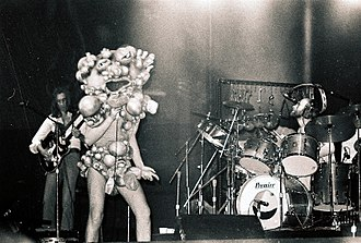 "Genesis (band) - Rutherford, Gabriel, and Collins in 1974 during The Lamb... tour. Gabriel is wearing the ""Slipperman"" costume."