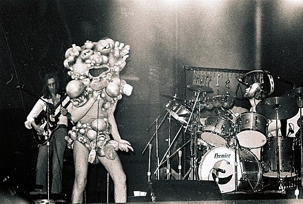 Genesis recreating their concept album The Lamb Lies Down on Broadway (1974) for a live performance. Band member Peter Gabriel is wearing a costume for one of the album's characters. Genesis live 1974-11-20.jpg