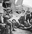 George Formby entertains troops in the ruins of a village in Normandy during an ENSA (Entertainments National Service Association) tour, 30 July 1944. B8256.jpg