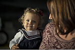 Gina Paige, right, holds her daughter as she waits at Mountain Home Air Force Base, Idaho, Oct. 3, 2013, for Staff Sgt. Josh Paige, an avionics shop technician with the 366th Aircraft Maintenance Squadron, to 131003-F-WU507-105.jpg