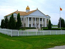 "A photograph of a two-story building. The roof is topped with a large cupola and three visible kalashes. Golden letters on the pediment say ""CAPITAL OF THE GLOBAL COUNTRY OF WORLD PEACE"". There is a circular driveway with a flagpole bearing the GCWP's sunburst flag. The building and drive are surrounded by a white picket fence, green lawn, and shrubbery."