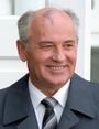 Un hombre con traje gris, camisa blanca y corbata oscura, calvo con cabello gris, tiene una marca de nacimiento en la frente.