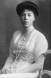 Black-and-white photograph of a young Olga seated in an Edwardian dress with a high neck line and long sleeves. Her thick dark hair is pinned up, and she wears a rope of pearls around her neck.