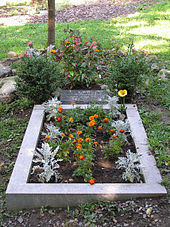 A rectangular stone slab bearing Lad's name and dates of birth and death lies above a rectangular plot of earth lined with concrete. Flowers are planted on the grave and around the slab.