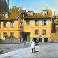 """Håndkolorert dias. En jente kledd i kjole står på gata foran en bygård i Vika, Oslo, i 1904. I bakgrunnen står tre andre små barn og en ung gutt. På bygården henger et skilt for """"Strandgadens Kul og (9456255859).jpg"""