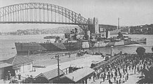 A two-funnelled cruiser slowly manoeuvring into position next to a wharf. Several small boats surround the cruiser, and a large crowd waits behind the wharf fence. The Sydney Harbour Bridge and northern shore of the harbour are in the background.
