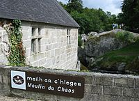"Side of a stone building next to a stream; low stone wall in the foreground has a sign reading ""Mill of Chaos"" in both Breton and French: ""Meilh ar C'hlegr"" and ""Moulin du Chaos"""