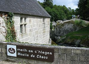 Side of a stone building next to a stream; low stone wall in the foreground has a sign reading Mill of Chaos in both Breton and French; Meilh ar C'hlegr and Moulin du Chaos