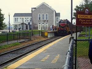 Hyannis Transportation Center - A Cape Cod Central Railroad train at the Hyannis Transportation Center station. The train is picking up passengers there because boarding using the lower platform of the Cape Cod Central's station (in the foreground) requires climbing stairs.