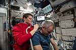 ISS-59 Anne McClain trims David Saint-Jacques' hair inside the Harmony module.jpg