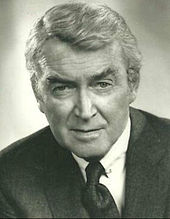A sepia-toned headshot of a silver-haired Stewart in a suit