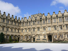 A regular pattern of windows and gables on two sides of a quadrangle of buildings; the matching shadows of the gables on the wall behind the photographer are visible on the snow