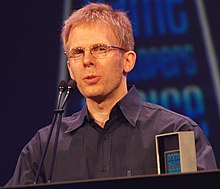 A man giving a speech after receiving an award for lifetime achievement at a game developers conference