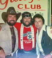 A group of three men with their arms round each other. The man on the left has a beard and is wearing a cowboy hat and a light-coloured vest. The one in the center has long hair and a beard and is wearing a bandana tied around his forehead, a red T-shirt and suspenders. The one on the right is wearing a white shirt and a dark vest.