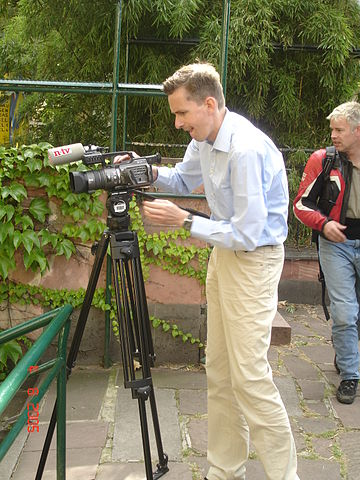 A journalist setting up his camera.