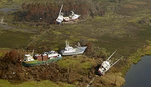 Bayou La Batre, Alabama - Cargo ship and boats aground at Bayou La Batre, Alabama, after Hurricane Katrina. The M/V Caribbean Clipper (left) was unloaded by crane six months later and refloated.