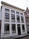 foto van Pand, bestaande uit twee huizen onder schilddaken, in het derde kwart 19e eeuw samengetrokken achter een gepleisterde lijstgevel ter breedte van vier vensterassen