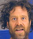 Neal head shot, straight on, with wild eyes, wild hair and wild beard.