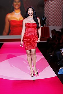 Kimora Lee on the runway, wearing a red dress by Kouture, 2010