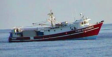 A small red fishing boat, without its usual tackle but with shipping containers at the rear, riding low astern in the open sea.