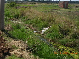 2008 Zimbabwean cholera outbreak - An open drain in Kuwadzana township, Harare in 2004. By 2008 drains such as this were carrying sewage from burst sewage pipes and feces washed out of the neighbouring areas as the urban sanitation system collapsed. This contributed to the rapid spread of the cholera outbreak.