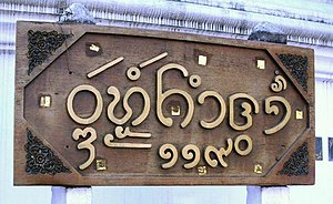 Tai Tham alphabet - Name board outside a Buddhist temple in Chiang Mai written with Lanna characters: Wat Mokhamtuang (and street number 119 in Thai)