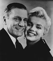 Close-up of smiling Monroe and Laurence Olivier, cheek-to-cheek. She is wearing long diamond earrings.