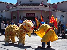 A costume lion and man in garb play fight at the Salinas Asian Festival, in front of the red and mauve confucius church