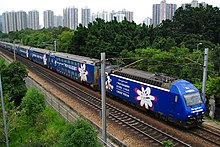 A dark blue color train with some advertising displays, in between green shrubs and two electricity cable holder poles, in the background some buildings appear