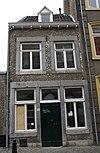 foto van Huisje met in de lijstgevel, vensters in Naamse steen, beneden gekoppeld aan weerskanten van de ingang.