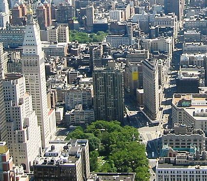 View looking south (downtown) from the Empire State Building at part of the Flatiron District. The Flatiron Building is the triangular building at right center, on the left is the Met Life Tower, with Madison Square Park below it. Between the park and the tower, at street level, Madison Avenue begins at 23rd Street and runs uptown (towards bottom). Madison Square is the intersection in front of the Flatiron, where Fifth Avenue and Broadway cross. (Fifth goes to the right of the building, and Broadway to the left.) The trees of Union Square Park can be seen at the top left center of the picture.