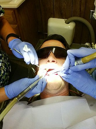 Dentist - A man being treated by dentists