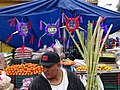 Man in Front of Fruit and Pinata Stand - San Miguel de Allende - Mexico (39272047841).jpg