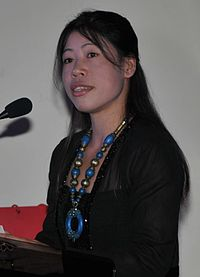 A photograph of Mary Kom looking slightly away from the camera while speaking on a microphone