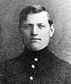 Head of a young man with thick, dark, hair parted at the side. He is wearing a military jacket with a high collar and bright buttons down the center.