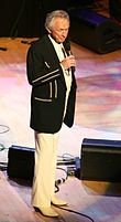 Man in white slacks and black jacket standing singing on stage