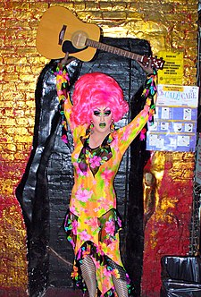 a drag queen, holding a guitar above her head. She has a bright pink wig on