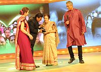 Mukesh Ambani and Nita ambani Felicitating Shobhana Ranade with Life Time Achievement Award.jpg