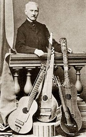 "Napoléon Coste - Napoléon Coste (1805–1883) with one of his Lacôte ""floating 7th string"" harp guitars, an 18th-century arch-cittern, a small terz(?) guitar, and a custom extra-large guitar."