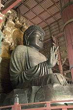 Three-quarter view and worm's-eye view of a seated statue. The palm of his right hand faces forward. The folds in his clothing are deeply sculpted. Behind the head of the sculpture there is a halo decorated with sitting statues. Color picture.