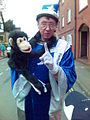 Old man in wizards costume with monkey (205086282).jpg