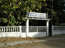 "A white gate with a sign reading ""Republique du Senegal: Prefecture d'Oussouye"""